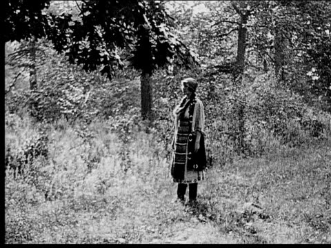 1916 b/w wide shot peasant woman walking in forest - menschliche gliedmaßen stock-videos und b-roll-filmmaterial