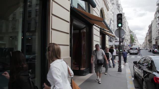 wide shot pedestrians and vehicles pass a hermes store operated by hermes international sca in paris france on saturday aug 9 signage and clockface... - hermes designer label stock videos and b-roll footage