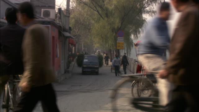 wide shot pedestrians, bikes, and traffic on narrow road/ beijing - ペディキャブ点の映像素材/bロール