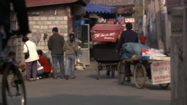 wide shot pedestrians, bikes, and traffic on narrow road intersection/ beijing - ペディキャブ点の映像素材/bロール
