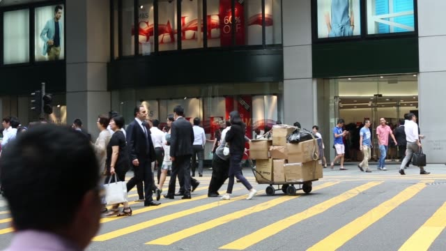 Wide shot pedestrians cross an intersection in front of a Marks Spencer Group Plc store in the central business district of Hong Kong China on...