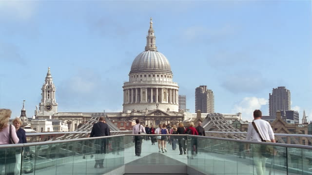 Wide shot pedestrians crossing Millennium Bridge with view of dome of St Paul's Cathedral / London