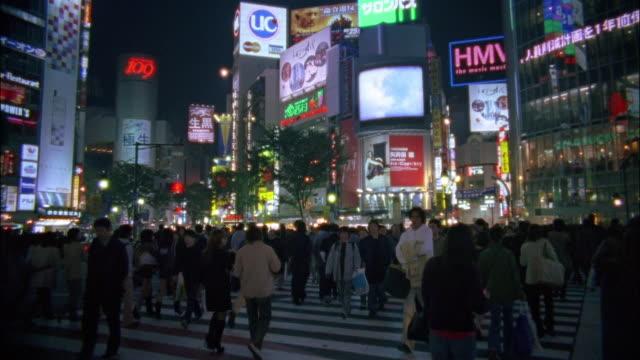 Wide shot pedestrians crossing street at Shibuya Crossing / Tokyo, Japan
