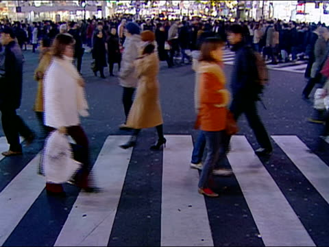 Wide shot pedestrians crossing street at Shibuya Crossing / Tokyo, Japan