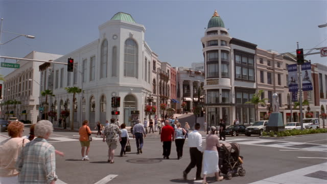 Wide shot pedestrians crossing street / Rodeo Drive / Beverly Hills, California