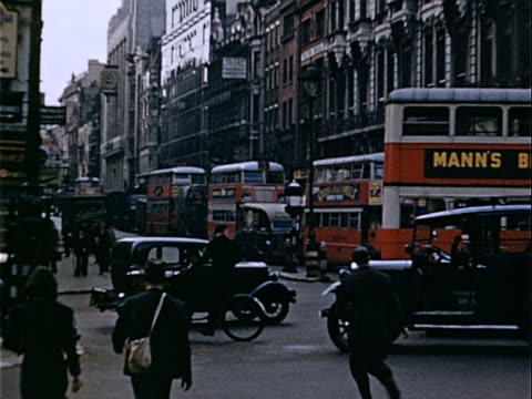 1939 Wide shot Pedestrians, double-decker buses and black taxis traveling on crowded city street / London, England