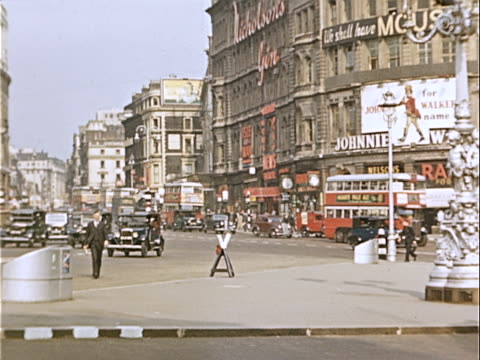 1939 Wide shot Pedestrians, double-decker buses and black taxis traveling on busy city street in Picadilly Circus / Westminster, London, England