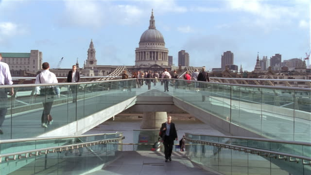 wide shot pedestrians on millennium bridge over thames with view of dome of st paul's cathedral / london - footbridge stock videos & royalty-free footage