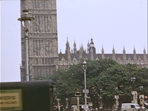 1939 wide shot pedestrians, police officers and trucks traveling on busy city street near houses of parliament and big ben / westminster, london, england - 1939 stock-videos und b-roll-filmmaterial