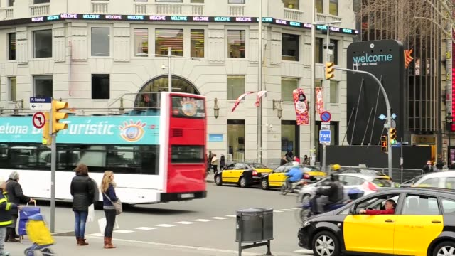 vídeos de stock, filmes e b-roll de wide shot pedestrians wait to cross busy city street taxi cabs and other traffic pass by digital ticker sign on exterior of building reads 'welcome... - sinal informativo