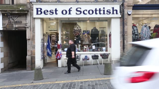Wide shot pedestrians walk along a street one man wearing a St Andrews or Saltire flag the national flag of Scotland on the day of the Scottish...