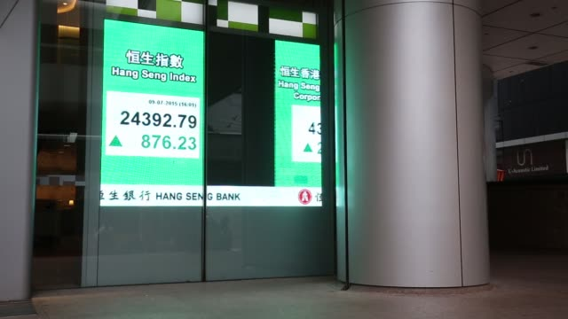 Wide shot pedestrians walk past the Hang Seng Index figure is displayed on a screen outside the Hang Seng Bank Ltd headquarters in Hong Kong China on...