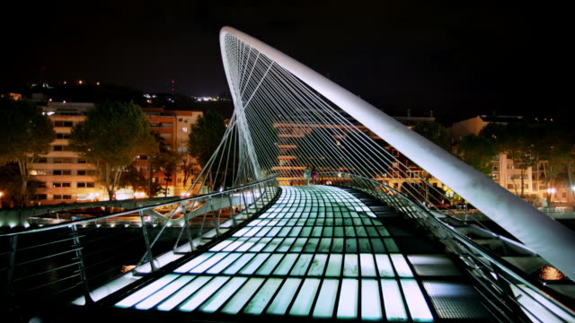 wide shot pedestrians walking across campo volantin footbridge, also known as zubizuri bridge/ bilbao, vizcaya province, spain - suspension bridge stock videos & royalty-free footage