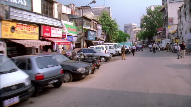 2001 wide shot pedestrians walking and cycling along busy city street/ delhi, india - 2001 stock videos & royalty-free footage