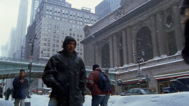 wide shot pedestrians walking in snow on 42nd street / grand central in background - 42nd street stock videos & royalty-free footage