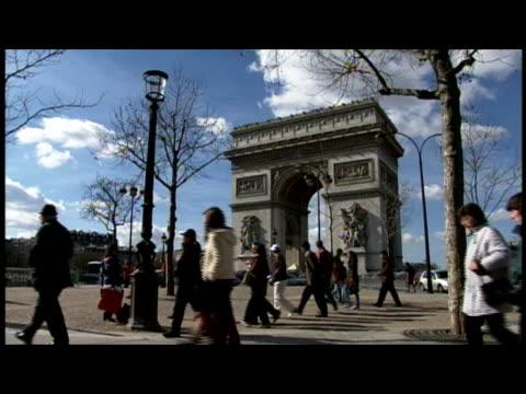 vidéos et rushes de wide shot pedestrians walking near arc de triomphe and traffic/ paris, france - arc élément architectural