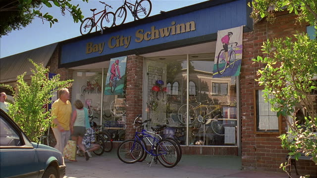 2001 wide shot pedestrians walking on sidewalk past bay city schwinn bicycle store/ seal beach, orange county, california, usa - banner stock videos & royalty-free footage
