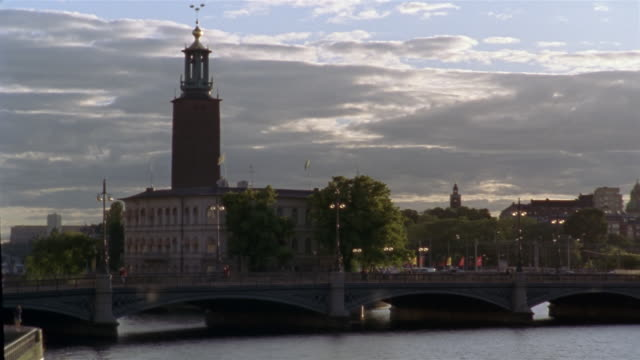 wide shot pedestrians walking on the stadshusbron bridge with stockholm city hall (stadshuset) in the background / stockholm, sweden - famous place stock videos & royalty-free footage