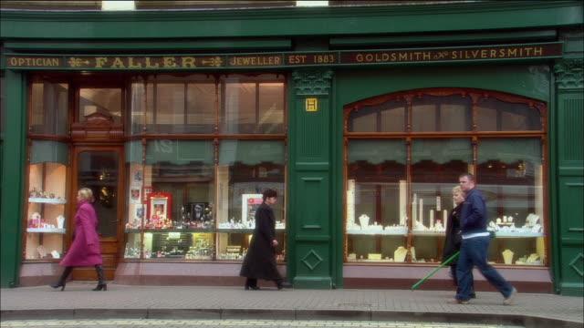 wide shot pedestrians walking past window display of jewelry store / derry, northern ireland - nordirland stock-videos und b-roll-filmmaterial