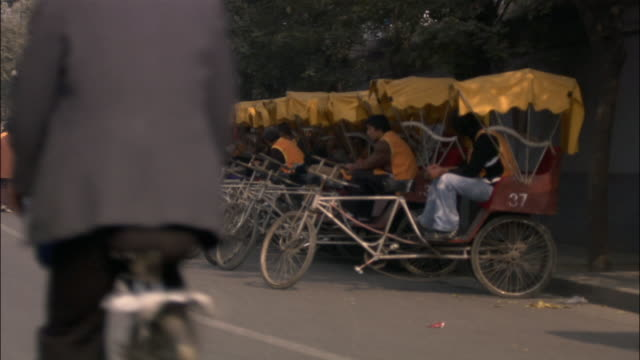 wide shot pedicabs in a row on curb as others ride down street/ beijing - ペディキャブ点の映像素材/bロール