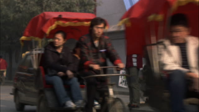 wide shot pedicabs passing by man standing on curb/ beijing - risciò video stock e b–roll