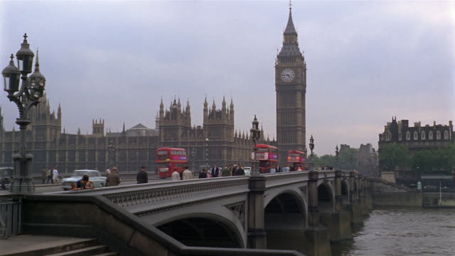 1966 wide shot people and cars on bridge with big ben in background / london, england - doppeldeckerbus stock-videos und b-roll-filmmaterial