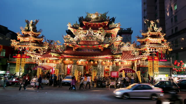 Wide shot people and traffic moving around entrance to Ciyou temple at twilight / Taipei, Taiwan