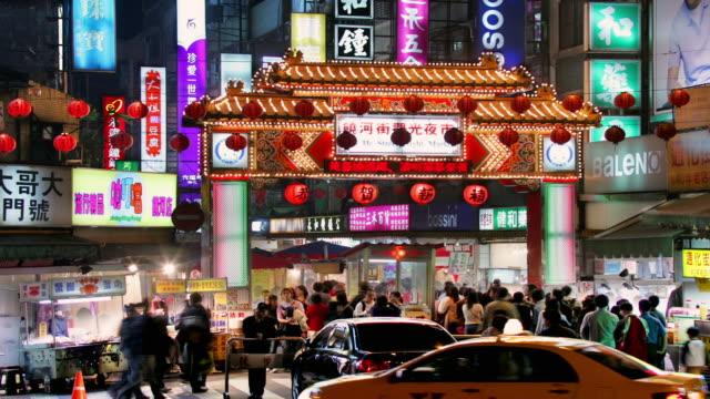 wide shot people and traffic passing by entrance to rao he street night market / taipei, taiwan - 台北市点の映像素材/bロール