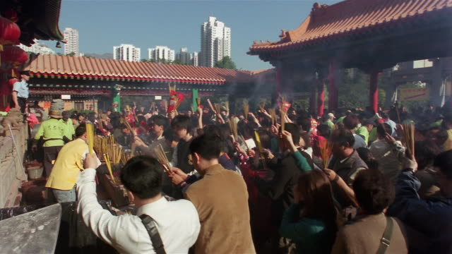 wide shot people burning incense sticks for good luck on chinese new year's day at wong tai sin temple/ kowloon, hong kong - 幸運点の映像素材/bロール