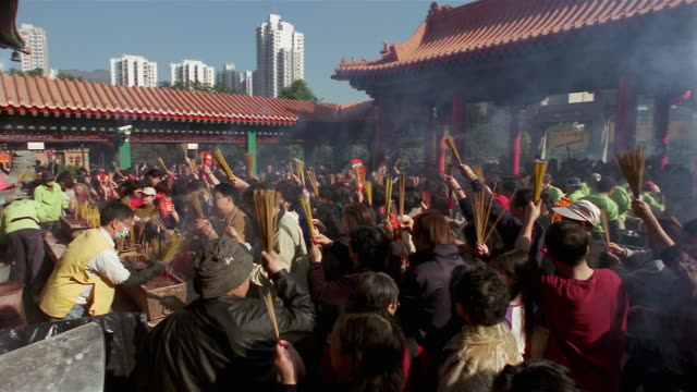 Wide shot people burning incense sticks on Chinese New Year's Day for good luck at Wong Tai Sin Temple/ Kowloon, Hong Kong