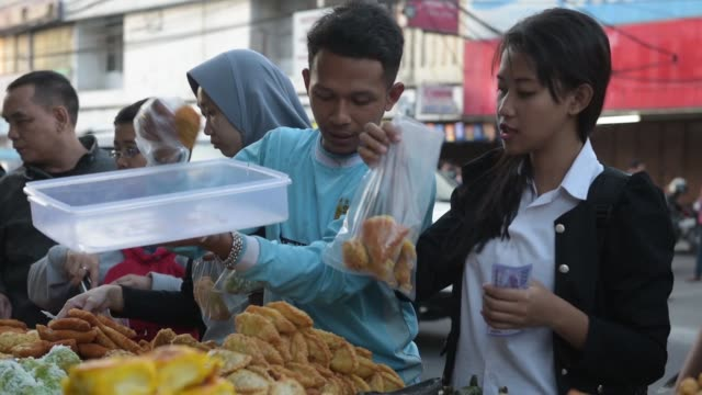 Wide shot people buy traditional snacks from food stalls a day before Eid alFitr in Jakarata Indonesia