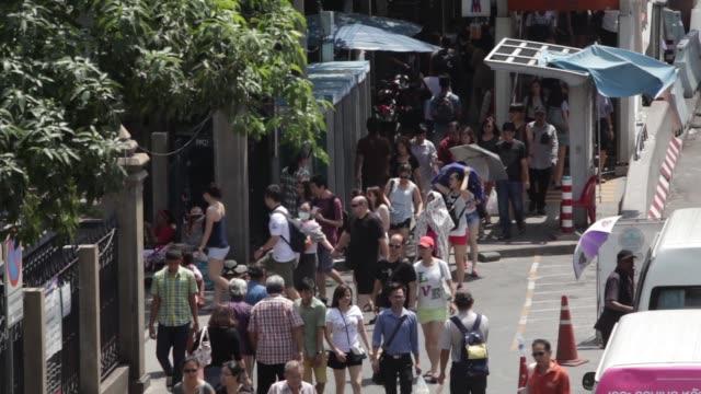 wide shot, people cross a footbridge over traffic traveling along a road in bangkok, wide shot, pedestrians walk along a road outside chatuchak... - bangkok stock videos & royalty-free footage