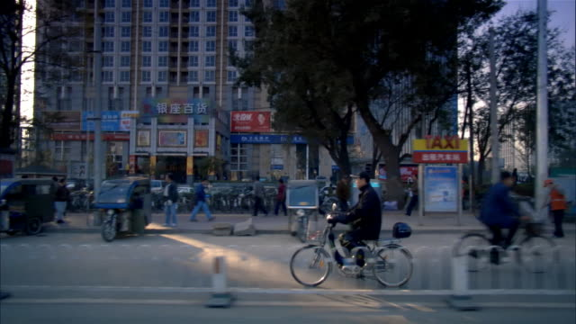 wide shot people cycling in traffic on city street/ beijing, china - bus billboard stock videos & royalty-free footage