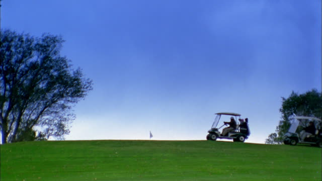 wide shot people driving golf carts on golf course at horizon line - golf cart stock videos & royalty-free footage