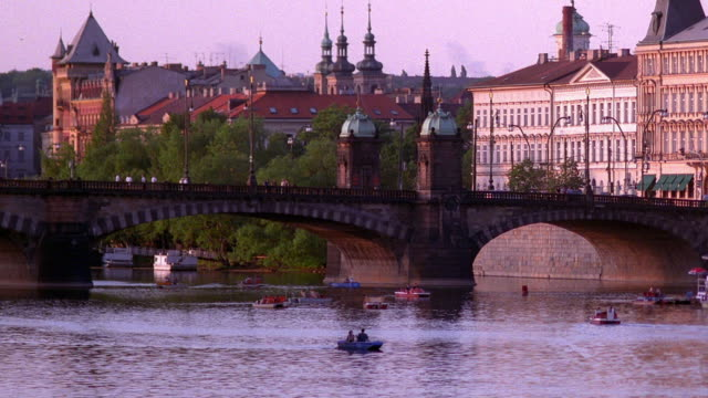 wide shot people in boats on vltava river with bridge and city in background / prague, czech republic - vltava river stock videos & royalty-free footage