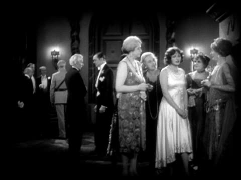 1928 b/w wide shot people in formalwear talking at social gathering  - gossip stock videos & royalty-free footage
