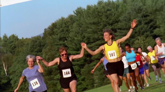 vídeos de stock, filmes e b-roll de wide shot people in race holding hands and crossing finish line / vermont - o fim