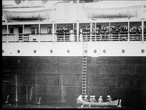 1914 b/w wide shot people in rescue boat rowing toward large cruise ship - passenger stock videos & royalty-free footage