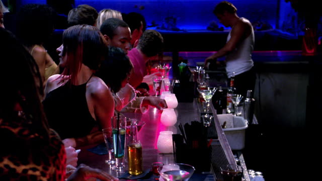 Wide shot people leaning over bar in nightclub and buying drinks
