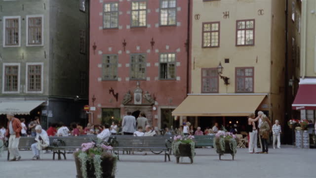 wide shot people milling around the stortorget / tilt up along iconic buildings surround the square / gamla stan, stockholm, sweden - bench stock videos & royalty-free footage