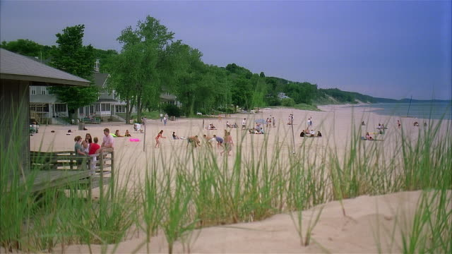 2001 wide shot people playing ball and sunbathing on beach in front of beach houses near shore of lake michigan/ grand haven, michigan, usa - great lakes stock videos & royalty-free footage