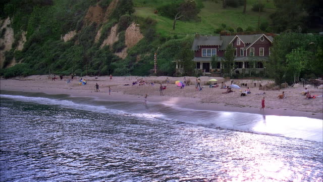 2001 wide shot people playing volleyball on beach in front of beach house near shore of lake michigan at dusk/ grand haven, michigan, usa - great lakes stock videos & royalty-free footage