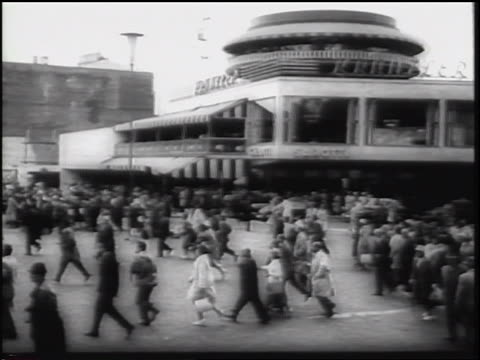 b/w 1961 wide shot pan people running toward crowdlined street during parade / berlin germany / newsreel - 1961 stock-videos und b-roll-filmmaterial