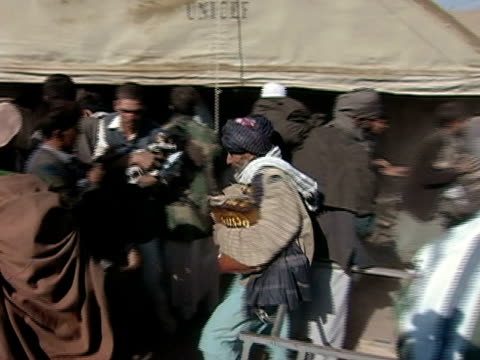 wide shot people stealing from unicef tent - operazione enduring freedom video stock e b–roll