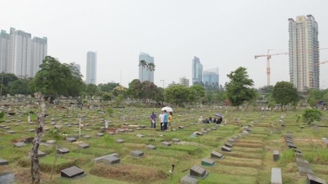 Wide shot people visit the graves of ancestors ahead of Ramadan at TPU Karet Bivak cemetery in Jakarta