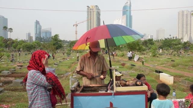 Wide shot people walk past street vendors selling food and drinks at TPU Karet Bivak cemetery in Jakarta