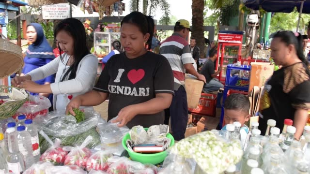 Wide shot people walk past street vendors selling food and drinks at TPU Karet Bivak cemetery in Jakarta A woman sells drinks and flowers at a stall...