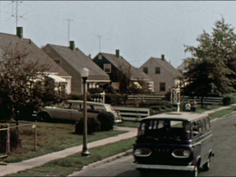 1964 wide shot people walking, a child bicycling, and cars driving down suburban street / long island, new york / audio - suburban stock videos & royalty-free footage