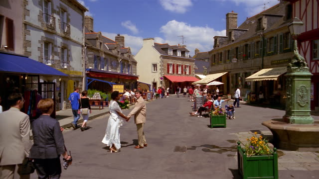 wide shot people walking along town street / concarneau - ブルターニュ点の映像素材/bロール