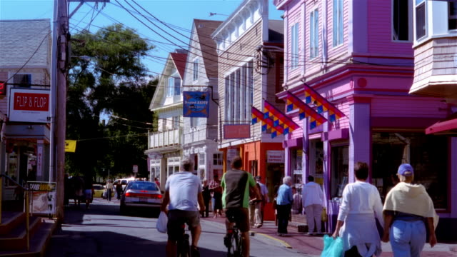 wide shot people walking and cycling in shopping district/ provincetown, massachusetts - rainbow flag stock videos & royalty-free footage